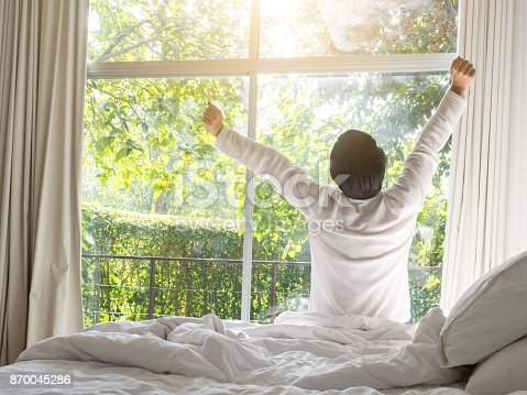 istock lazy man happy waking up in the bed rising hands to window in the morning with fresh feeling relax 870045286