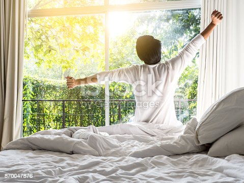 istock lazy man happy waking up in the bed rising hands to window in the morning with fresh feeling relax 870047876