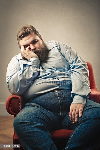 istock Lazy man in his chair 693313726