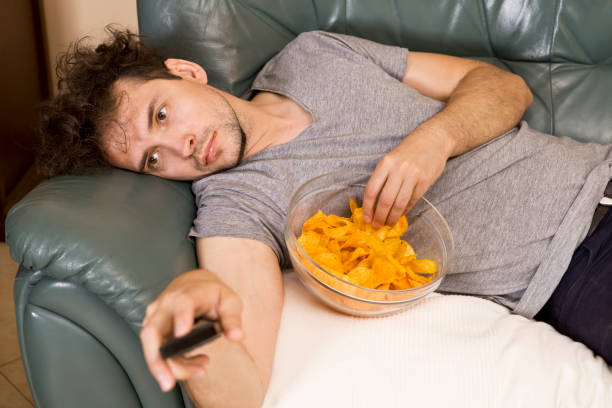 lazy man with the remote and chips on the couch - sloth stock pictures, royalty-free photos & images