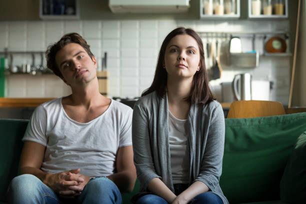 lazy millennial couple getting bored at home sitting on sofa - divano procrastinazione foto e immagini stock