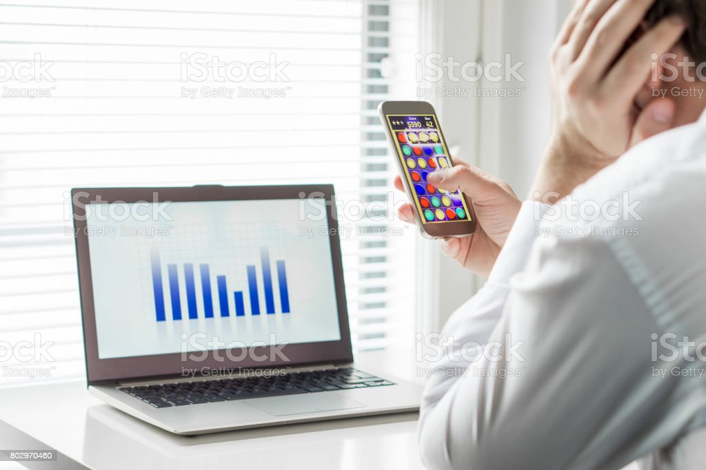 Lazy office worker playing mobile game with smartphone during work hours. Avoiding his job and leaning head against hand. Bored employee. Useless and unproductive man doing nothing and forget his job. stock photo