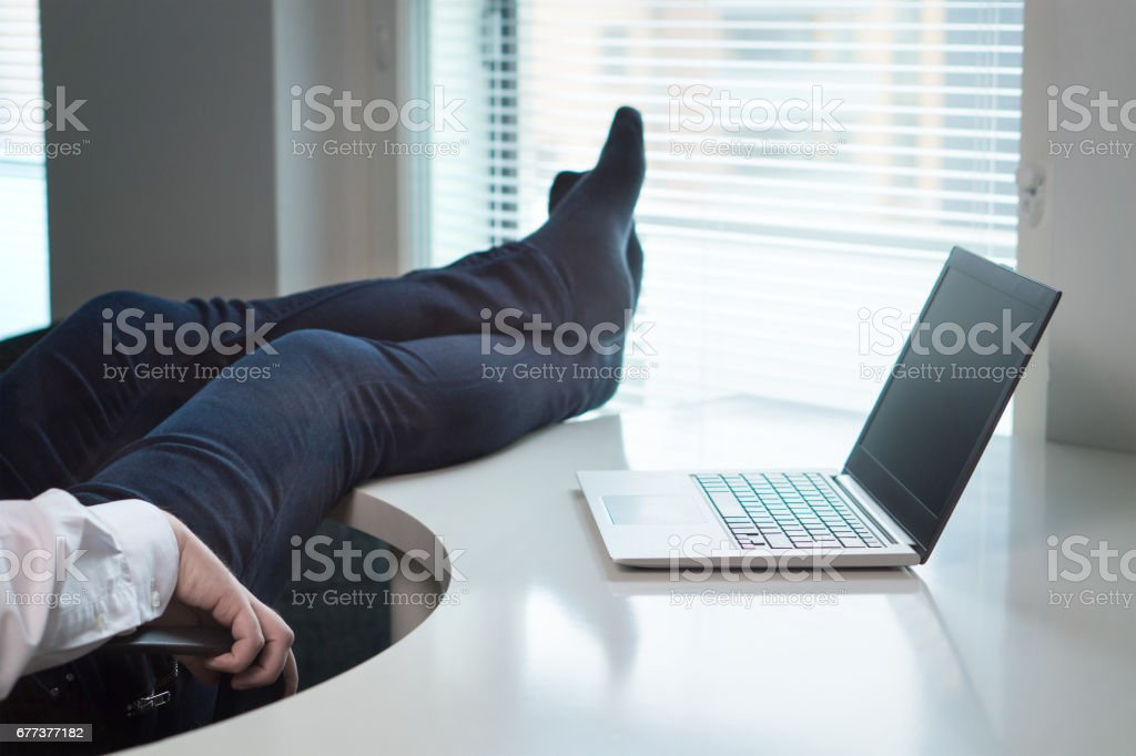 Lazy office worker with feet and socks on table. Useless and relaxing man doing nothing or taking break from work in workstation. Businessman resting during workday. Laziness and relax concept. stock photo