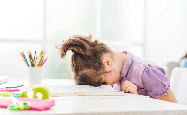 Lazy student girl at home Lazy student girl at home, she is resting with her face down on the school book, education and childhood concept face down stock pictures, royalty-free photos & images