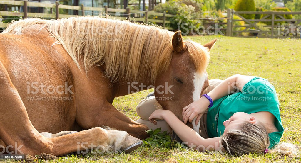 Lazy sunny summers days-girl and pony relaxingtogether. stock photo
