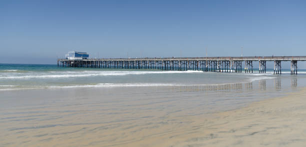 Lazy surf ate Newport Beach with Pier at horizon line. stock photo