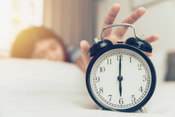 lazy to wake up girl hand off alarm clock ring on bed at morning monday - squillare foto e immagini stock