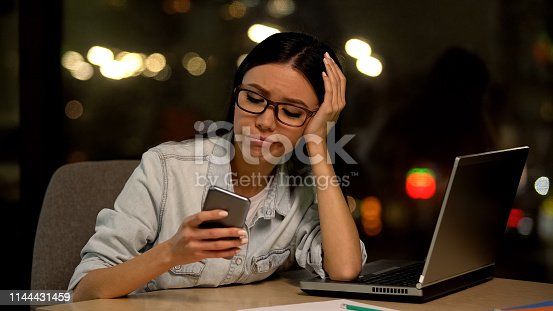 593328060 istock photo Lazy woman using cell phone at workplace, avoiding boring job, distraction 1144431459