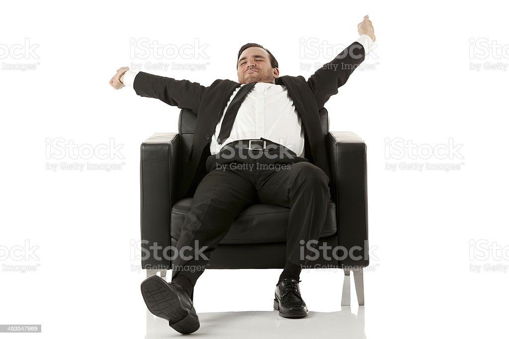 Lazy young businessman sitting on armchair royalty-free stock photo