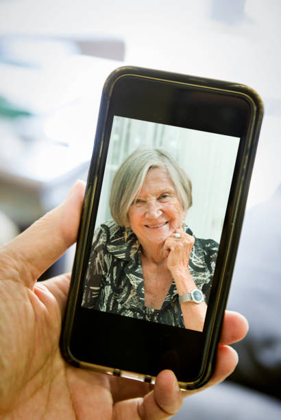 lCOVID-19 Shelter in Place and Social Distancing in effect, Virtual Caring for Senior Parents through Live Streaming, video Conferencing Virtual Gathering stock photo