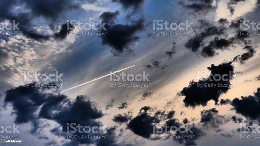 Le ciel et les nuages illuminés par le soleil avec une traînée d'avion stock photo
