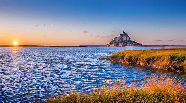 Le Mont Saint-Michel at sunset, Normandy, France Panoramic view of famous Le Mont Saint Michel tidal island in beautiful golden evening light at sunset in summer, Normandy, France. manche stock pictures, royalty-free photos & images
