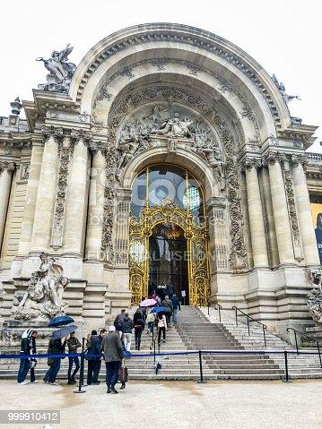 Paris, France - April 29, 2018: Le Petit Palais, Museum. People waiting in line with umbrellas to visit Exhibitions