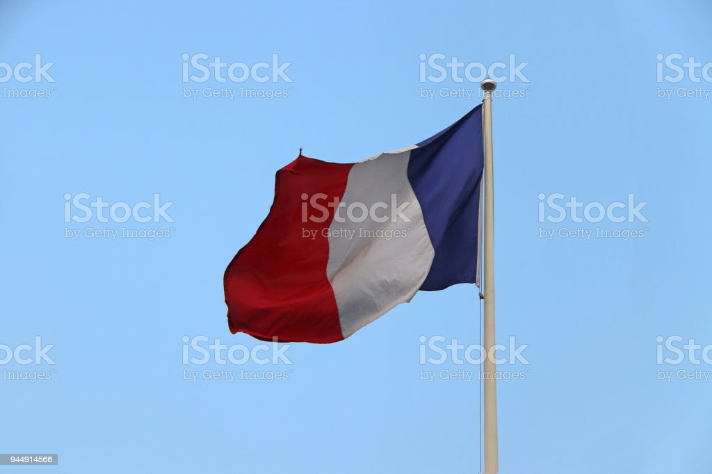 le tricolore or Tri Color of French Flag, le drapeau bleu-blanc-rouge or blue white and red color with on blue sky background. stock photo