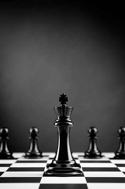 leader, schwarze könig vor schach pawns auf dunklem hintergrund - hochkönig stock-fotos und bilder