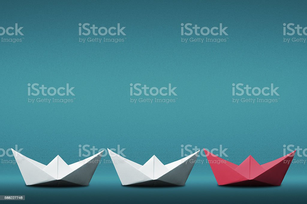 Red leader paper boat leading white ones. Three ships sailing on blue...