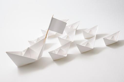 Leader ship of white paper boats fleet on white background