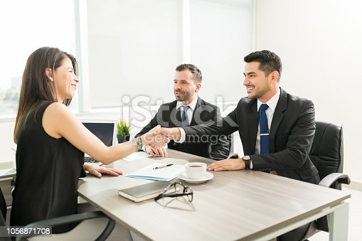 1008974324 istock photo Leader Welcoming Partners With A Handshake In Office 1056871708
