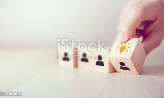 istock Leader with idea and innovation, Woman hand flips cube with icon light bulb and human symbol. 1154826797