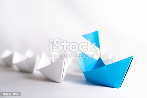 istock Leadership concept. blue paper ship with flag lead among white. One leader ship leads other ships. 1003225576