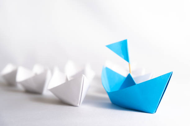 leadership concept. blue paper ship with flag lead among white. one leader ship leads other ships. - przewodzić zdjęcia i obrazy z banku zdjęć