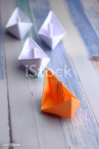 leadership concept with paper boat on  table