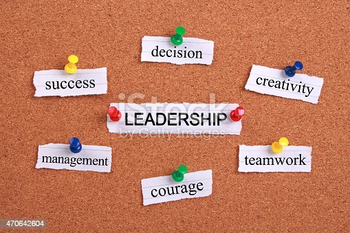 Leadership concept paper words are pinned on cork.
