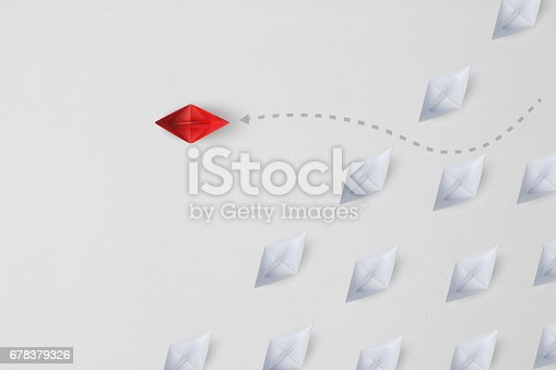 Business concept  as a group of paper ship in one direction and with one individual pointing in the different way as icon for innovative solution.