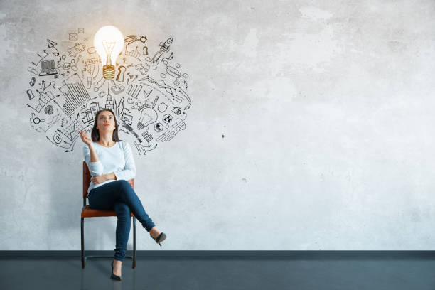 Leadership concept Thoughtful young woman sitting in concrete interior with creative business sketch and shadow. Leadership concept brainstorming stock pictures, royalty-free photos & images
