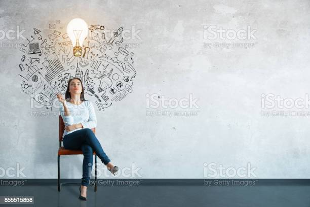 Thoughtful young woman sitting in concrete interior with creative business sketch and shadow. Leadership concept