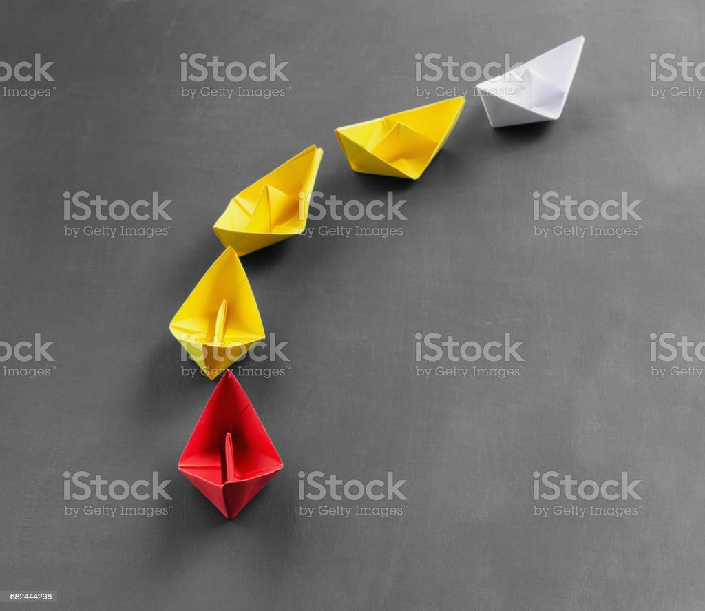 Leadership concept red leader paper boat standing out from the crowd of yellow boats foto de stock libre de derechos