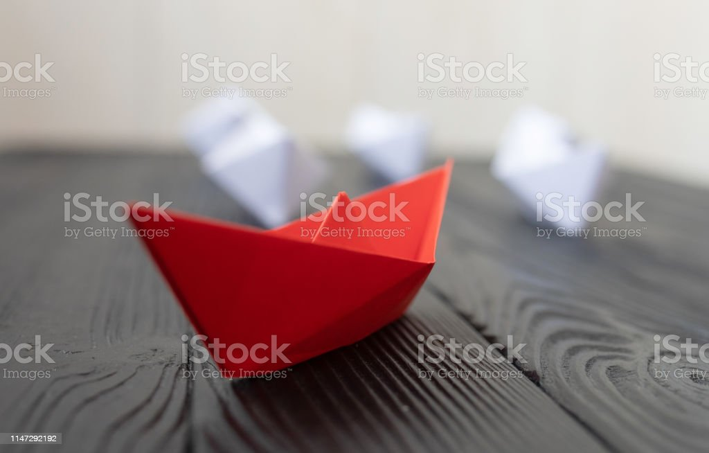 Leadership concept. Red leader paper ship leading among white on...