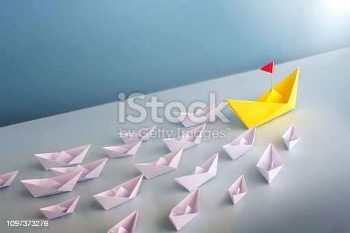 A group of origami white boat cruising to one direction lead by a bigger yellow boat.