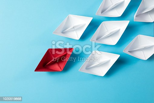 Leadership concept with a red paper ship leading among white ships on blue background