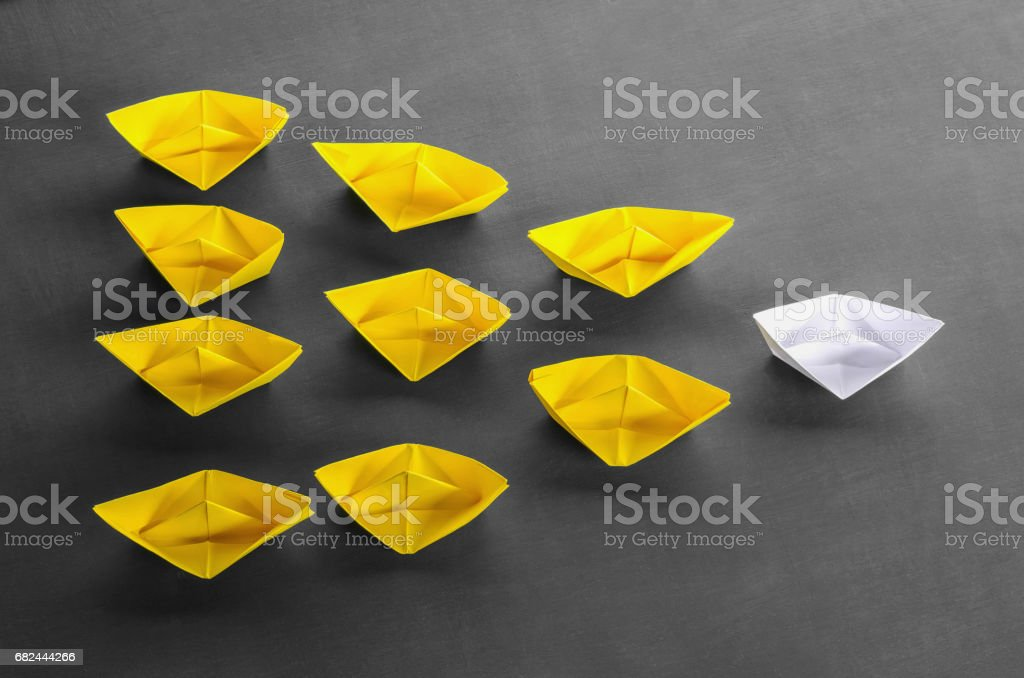 Leadership concept white leader paper boat standing out from the...