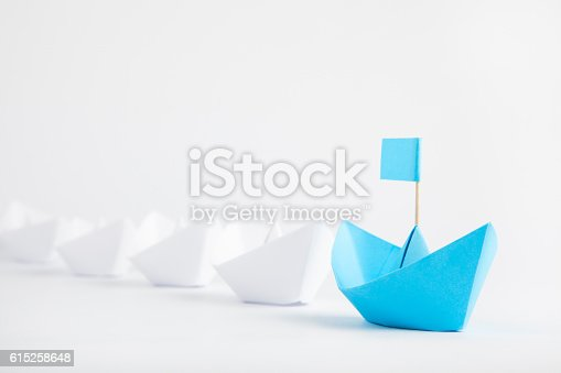 istock Leadership concept with blue paper ship leading among white 615258648