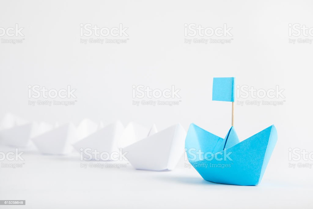 Leadership concept with blue paper ship leading among white bildbanksfoto