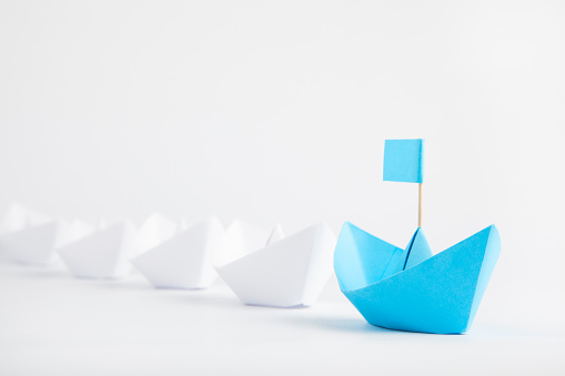 Leadership Concept With Blue Paper Ship Leading Among White Foto de stock y más banco de imágenes de Adulto