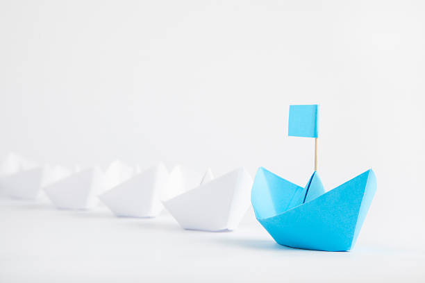 leadership concept with blue paper ship leading among white - computertaste stock-fotos und bilder