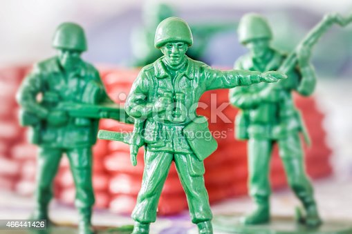 istock Leadership concept with little green armed soldier toy 466441426