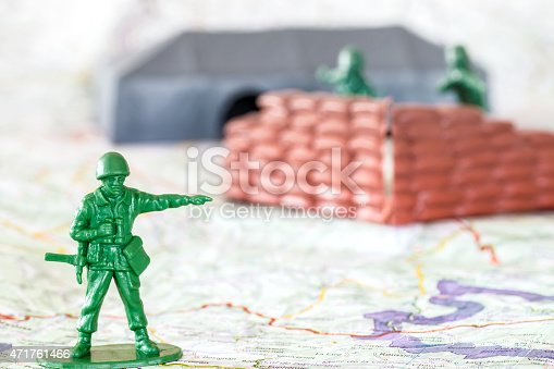 Concept of war, strategy with little green plastic figurine soldier toy behind a sandbag wall on battlefield with blurred soldier by selective focus in background. Concept of leadership, with little green soldier toy aiming the way forward, teamwork, macro shot in selective focus on the leader, shot on map floor with copy space.