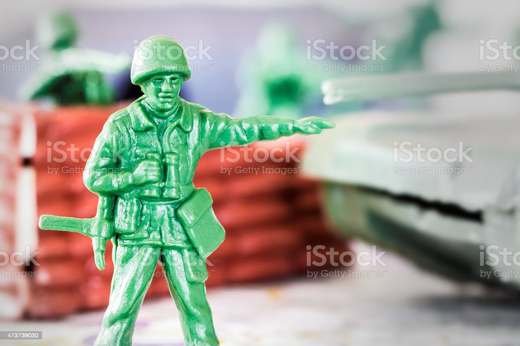 Leadership concept with little green armed soldier toy stock photo