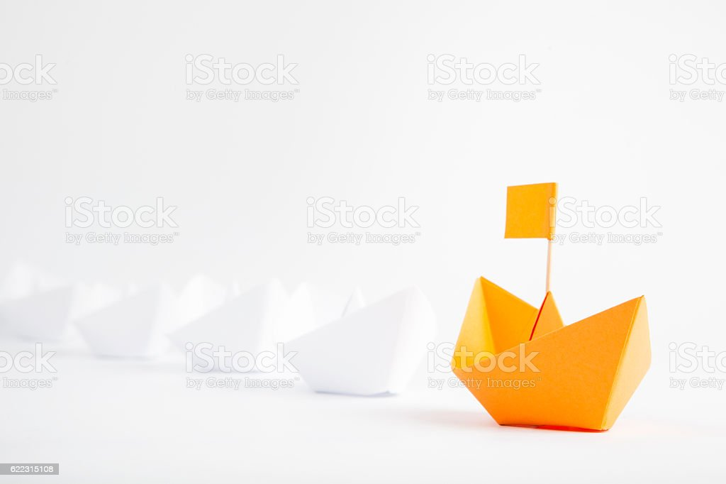 Leadership concept with orange paper ship leading among white stock photo