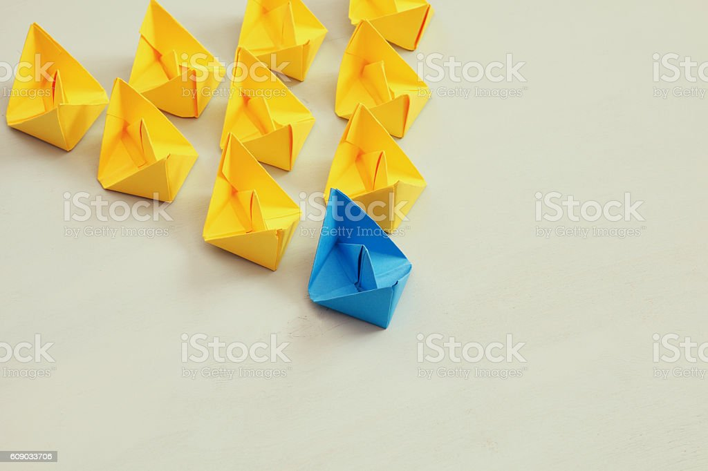Leadership concept with paper boats on wooden background stock photo