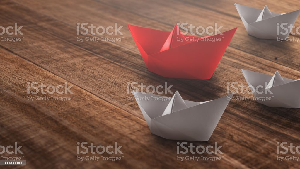 Leadership concept with red paper ship leading among the white on a...