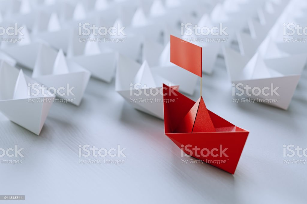 Leadership concept with red paper ship leading among white on white...