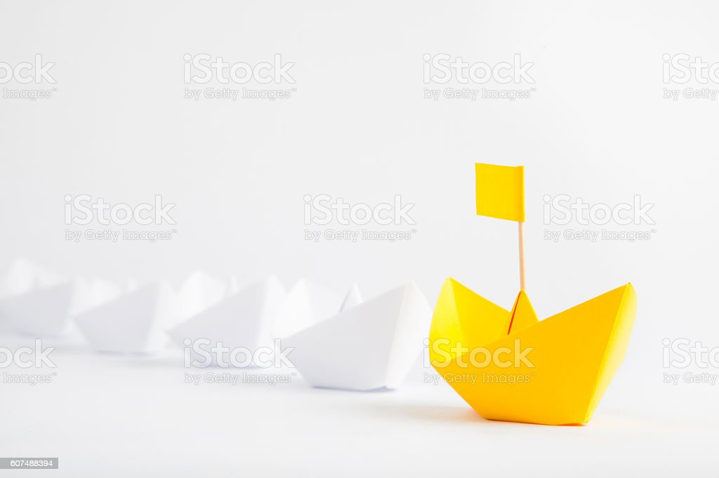 Leadership concept with yellow paper ship leading among white ships stock photo