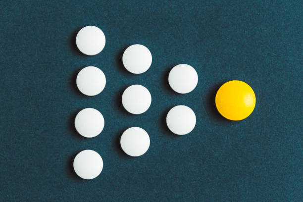 Leadership concept with yellow pill leading among white on blue background Leadership concept with yellow pill leading among white on blue background antihistamine stock pictures, royalty-free photos & images