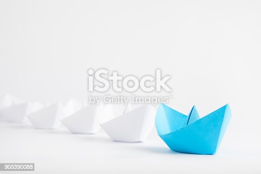 istock Leadership concepts with blue paper ship leading among white 905390088