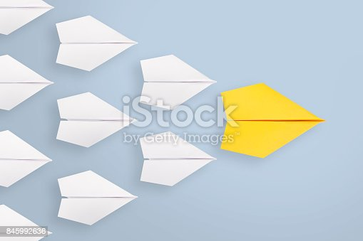 istock Leadership concepts with yellow paper plane leading among white 845992636